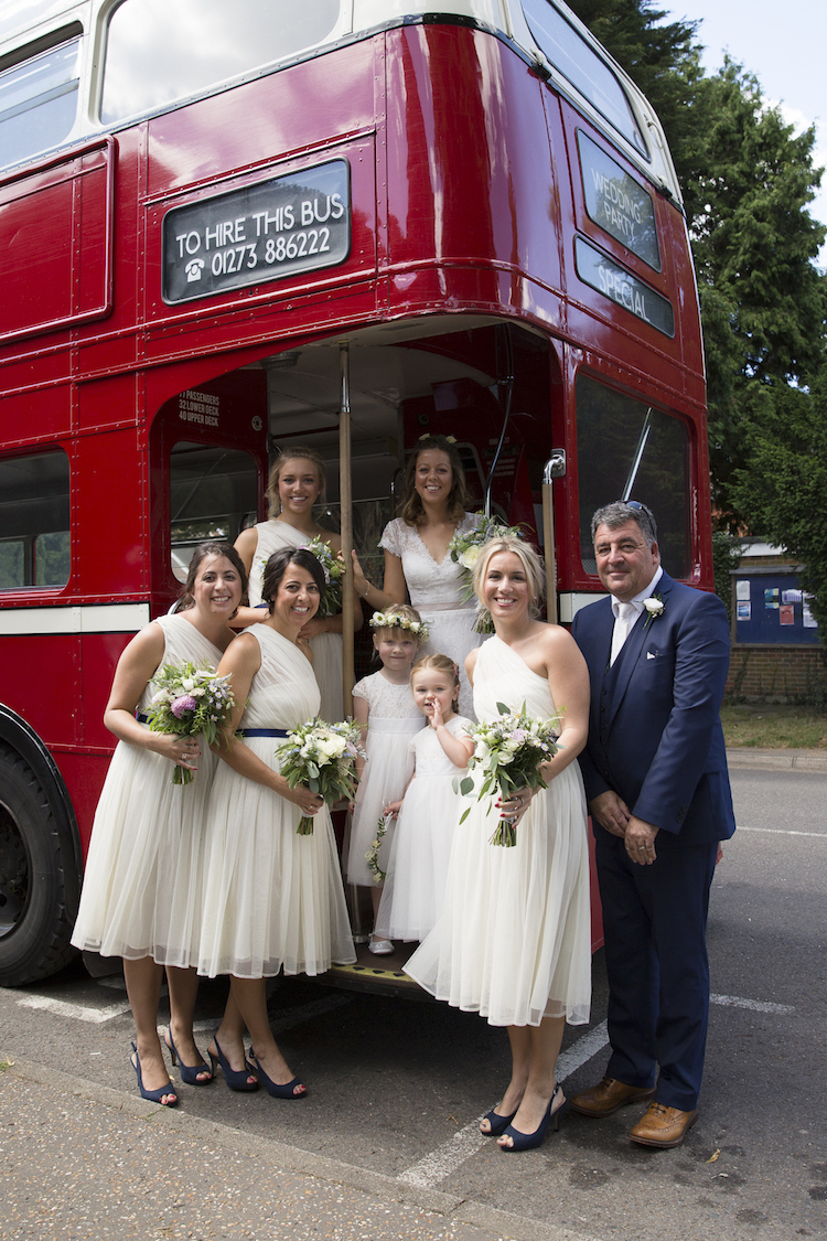 vintage wedding bus sussex with bridal party and flowers