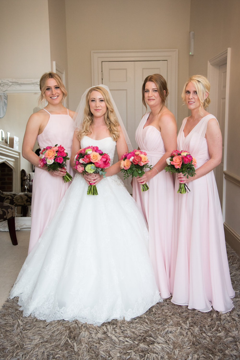 peach, coral and pink bouquets with blush bridesmaids dresses
