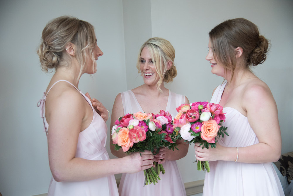 bridesmaids in pale pink dresses with bright flowers