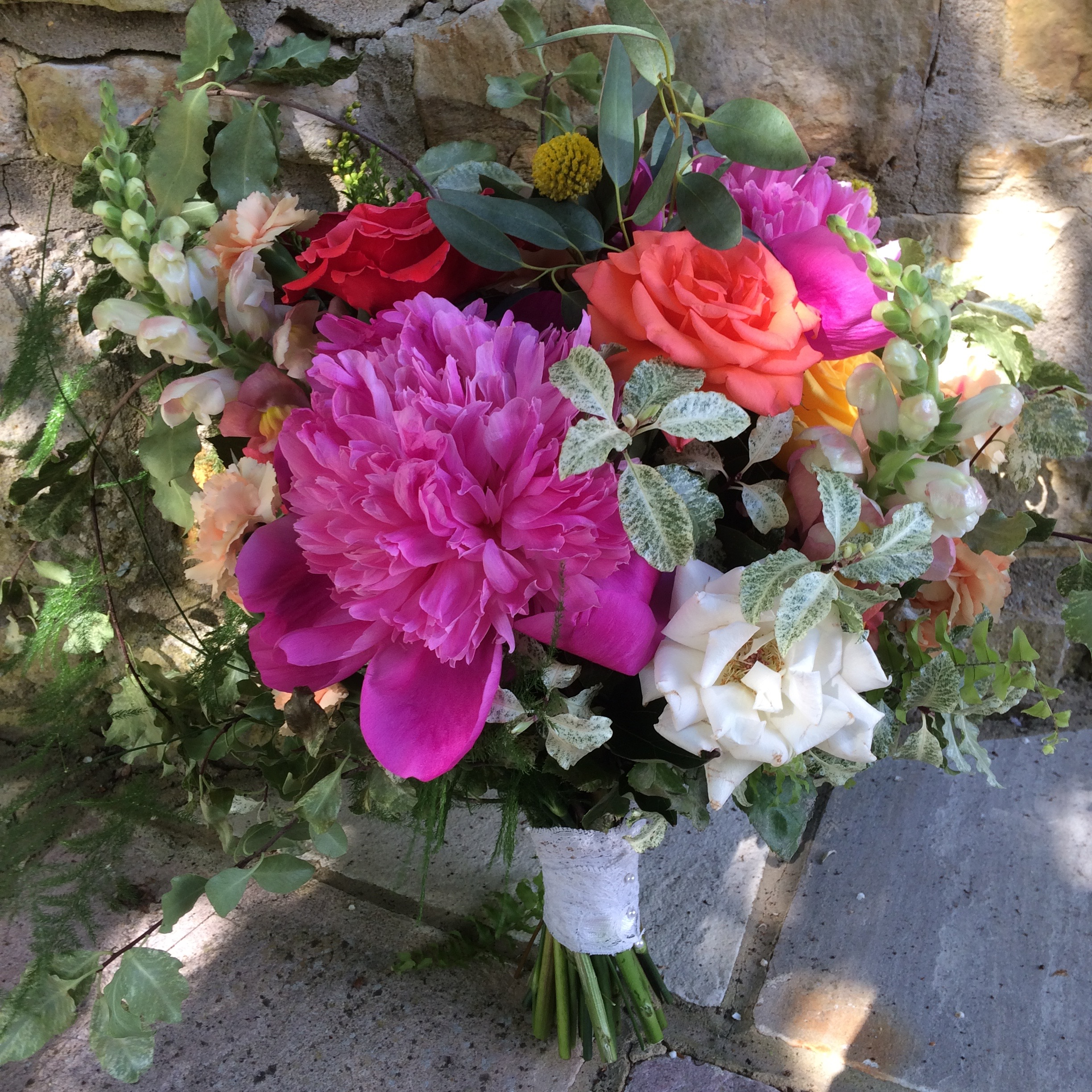 colourful bridal bouquet in June with peonies and English roses