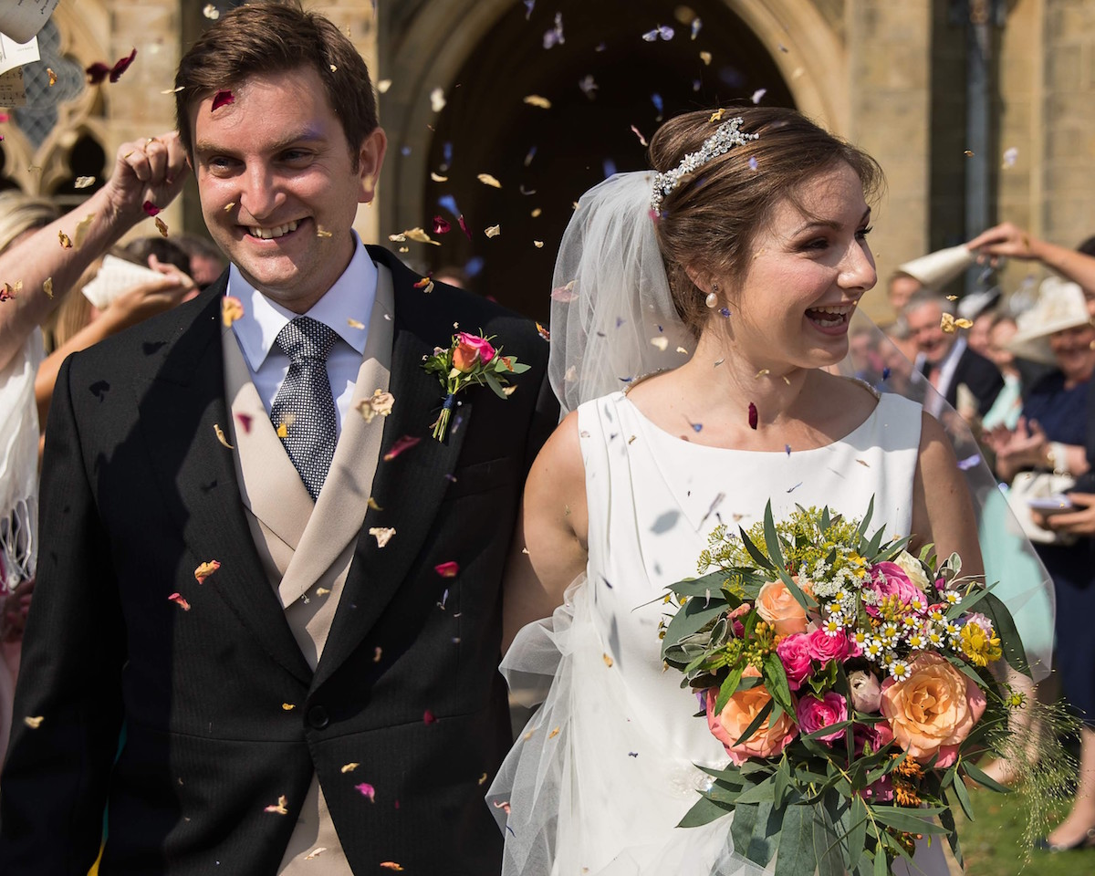 bride and groom with bouquet and confetti at Lancing College
