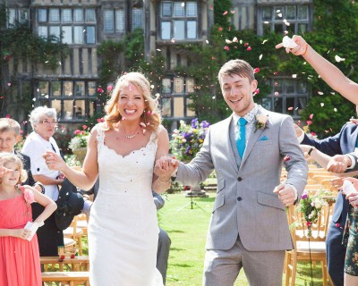 Bride and groom with confetti at great ote hall sussex. Country garden style wedding flowers.
