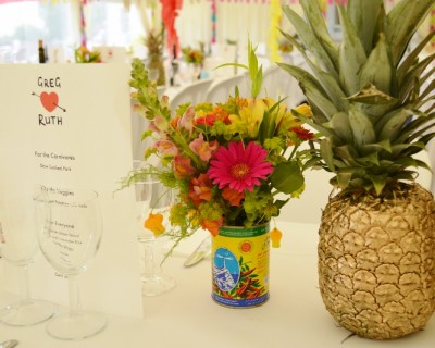 Tropical wedding flowers, gold pineapple table decorations.