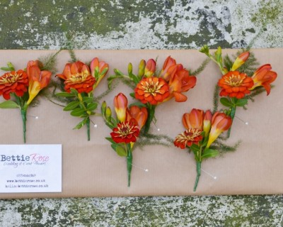 Orange freesia and zinnia buttonholes. Wedding flowers Brighton.