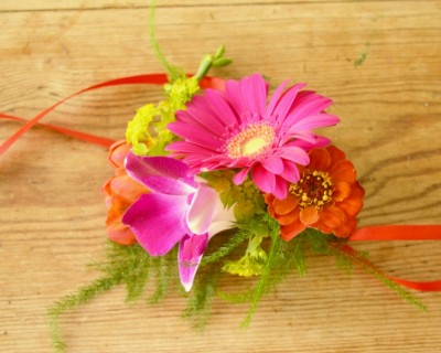 Pink and orange wrist corsage. Tropical wedding flowers. Brighton, Sussex florist