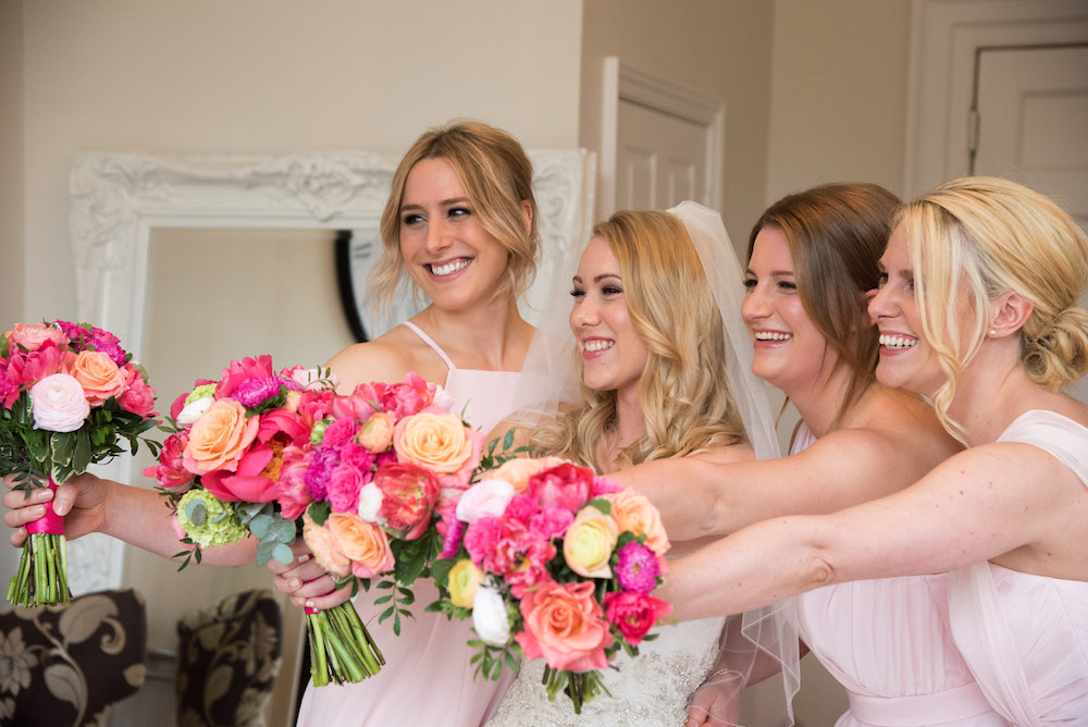 bridesmaids with bright pink and peach flowers with blush pink dresses