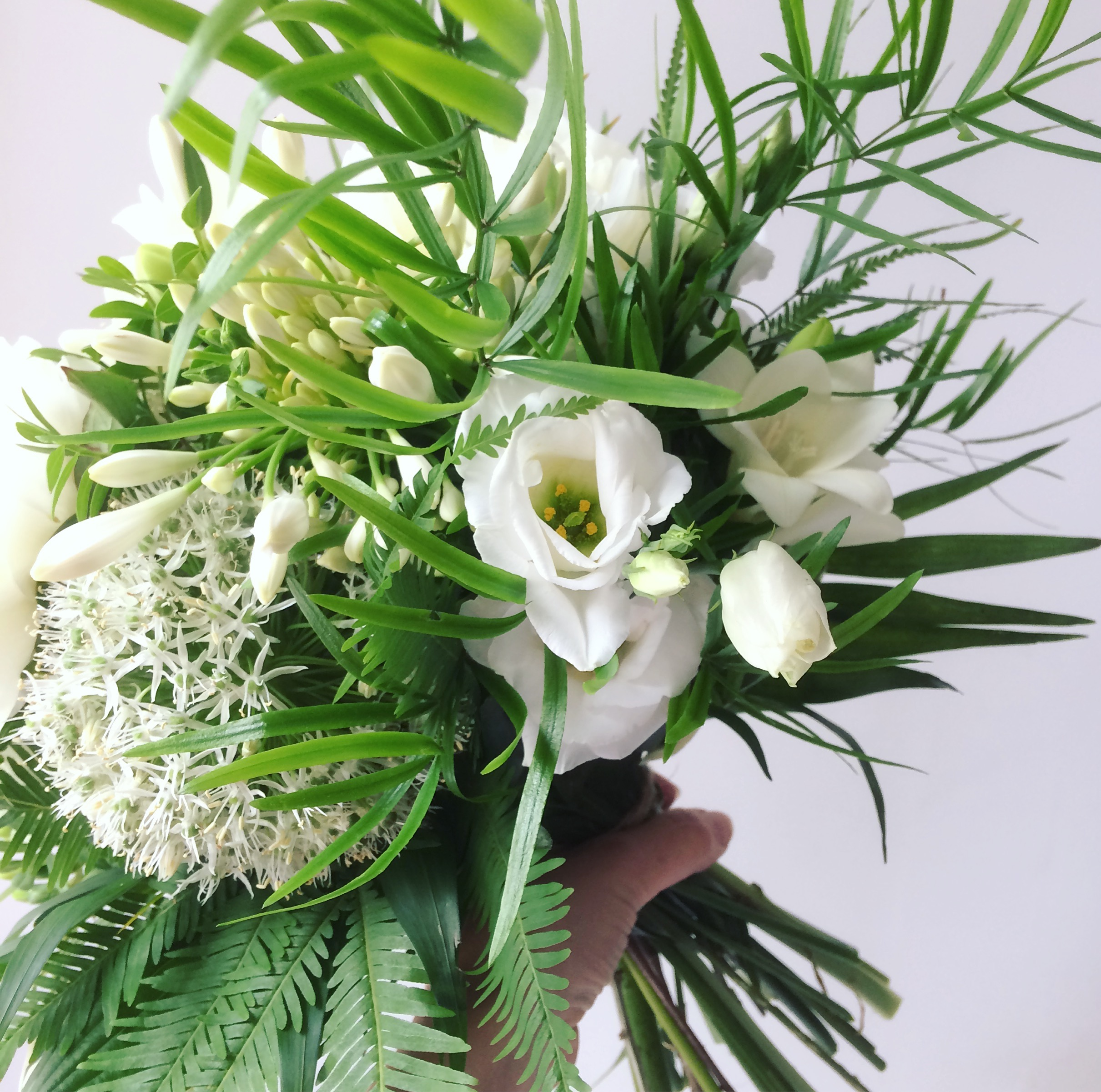 white and green bridal bouquet with ferns for a june wedding