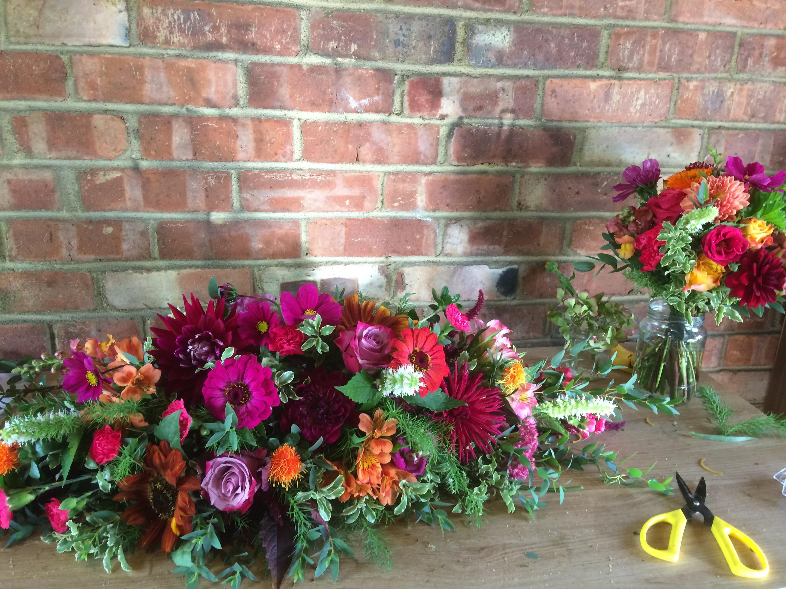 top table arrangement in hot pinks and oranges, autumn colours