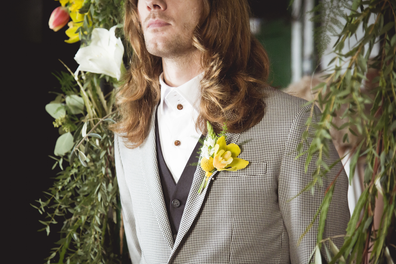 rock n roll groom, long hair and yellow buttonhole