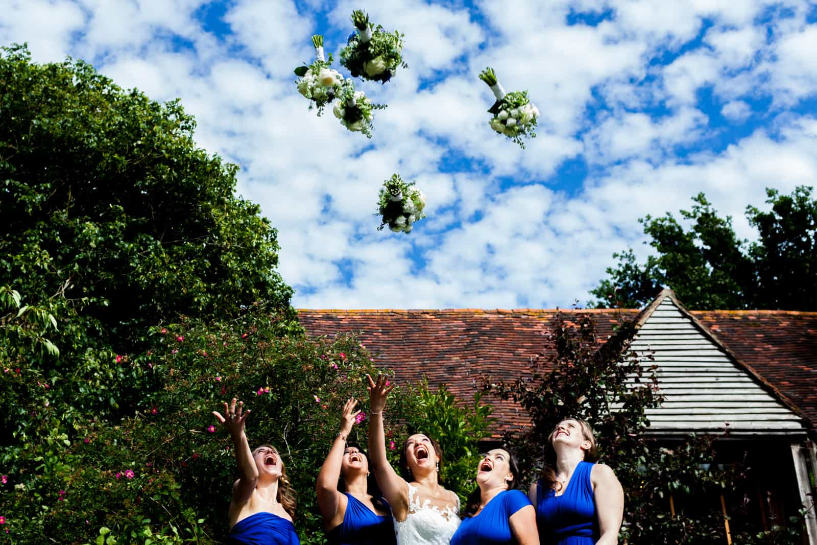 bride and bridesmaids throwing their bouquets in the air at The English Wine Centre