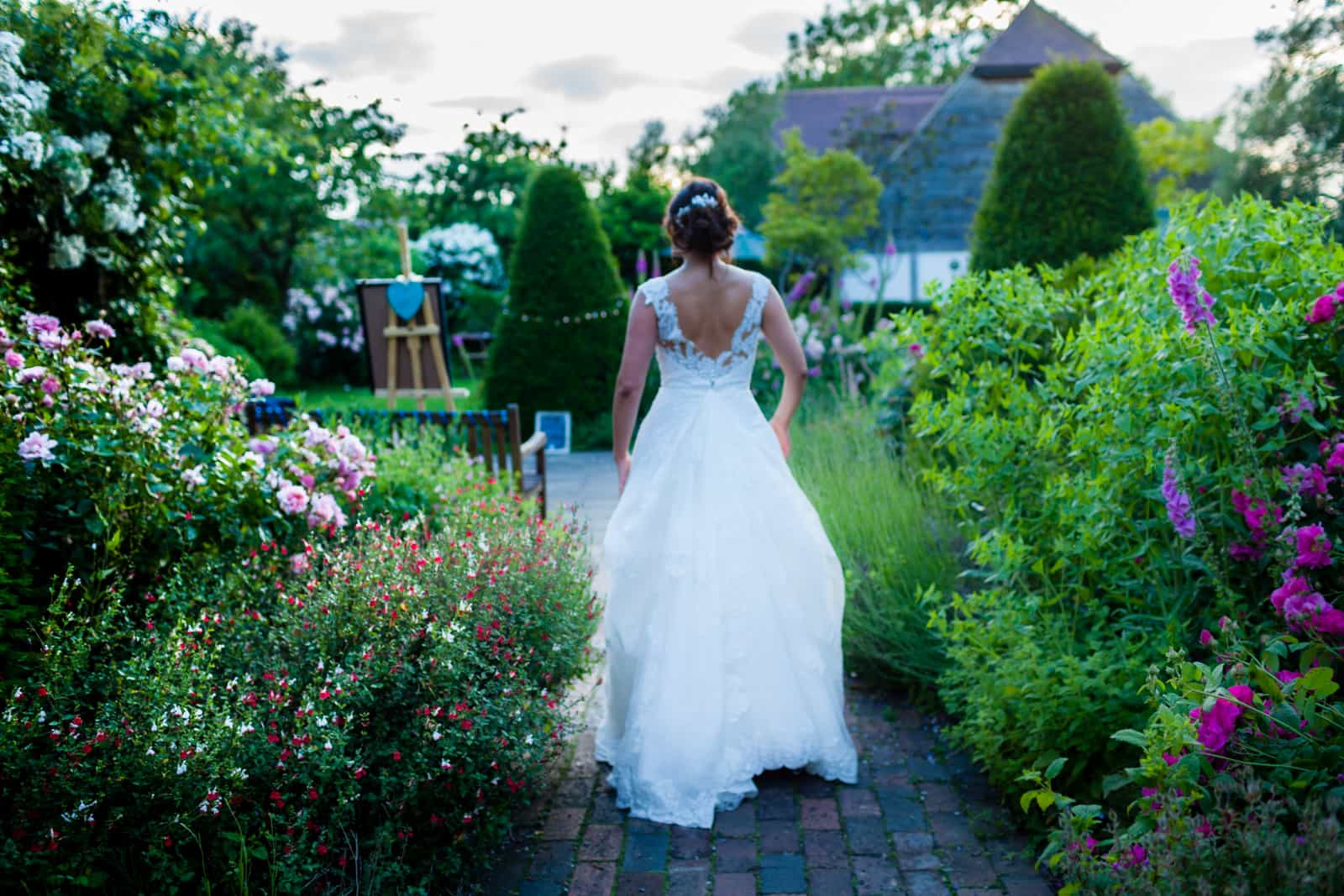 Bride walking through the rose garden at The English Wine Centre