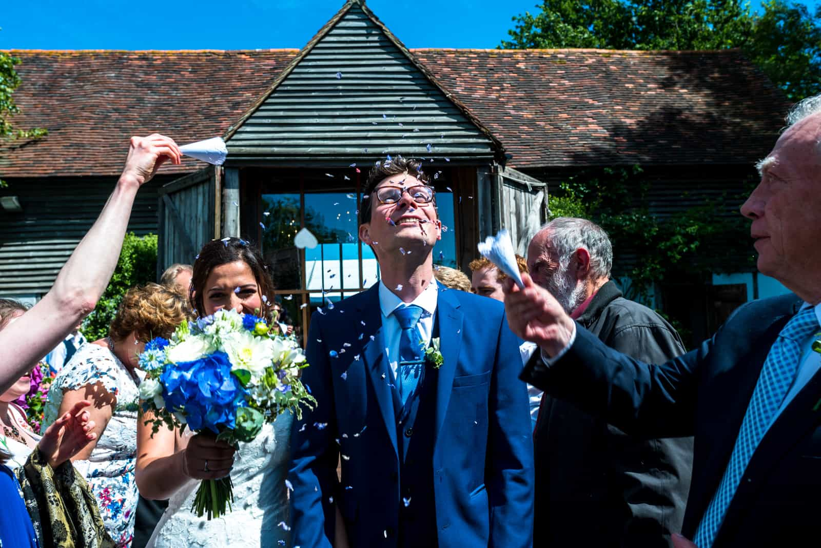 Bride and groom with flowers and confetti at East Sussex Wedding Venue