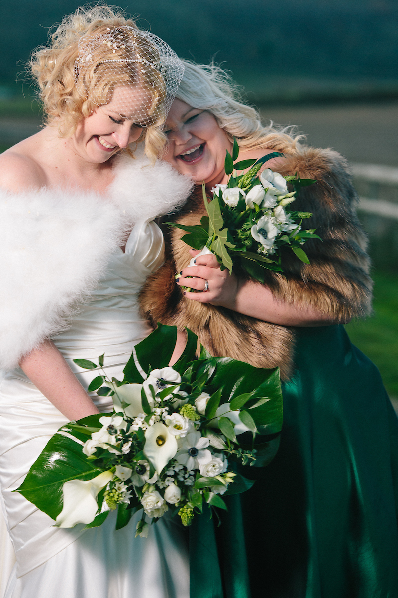 bride and bridesmaids with faux fur coats at long furlong barn sussex
