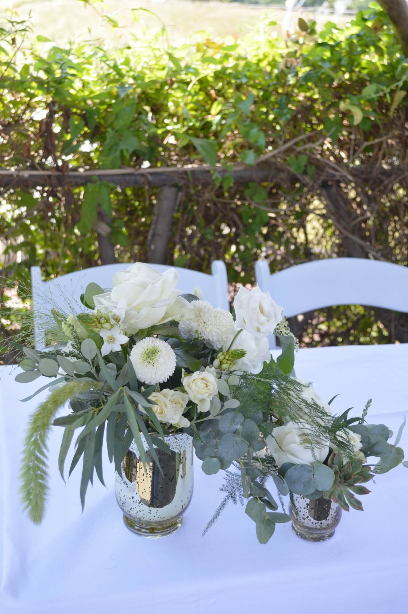 small gold vases with natural style white flowers and foliage