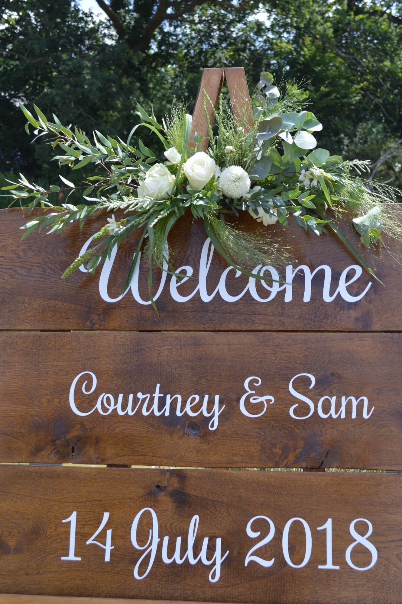 boho wooden welcome sign for wedding with white roses and eucalyptus