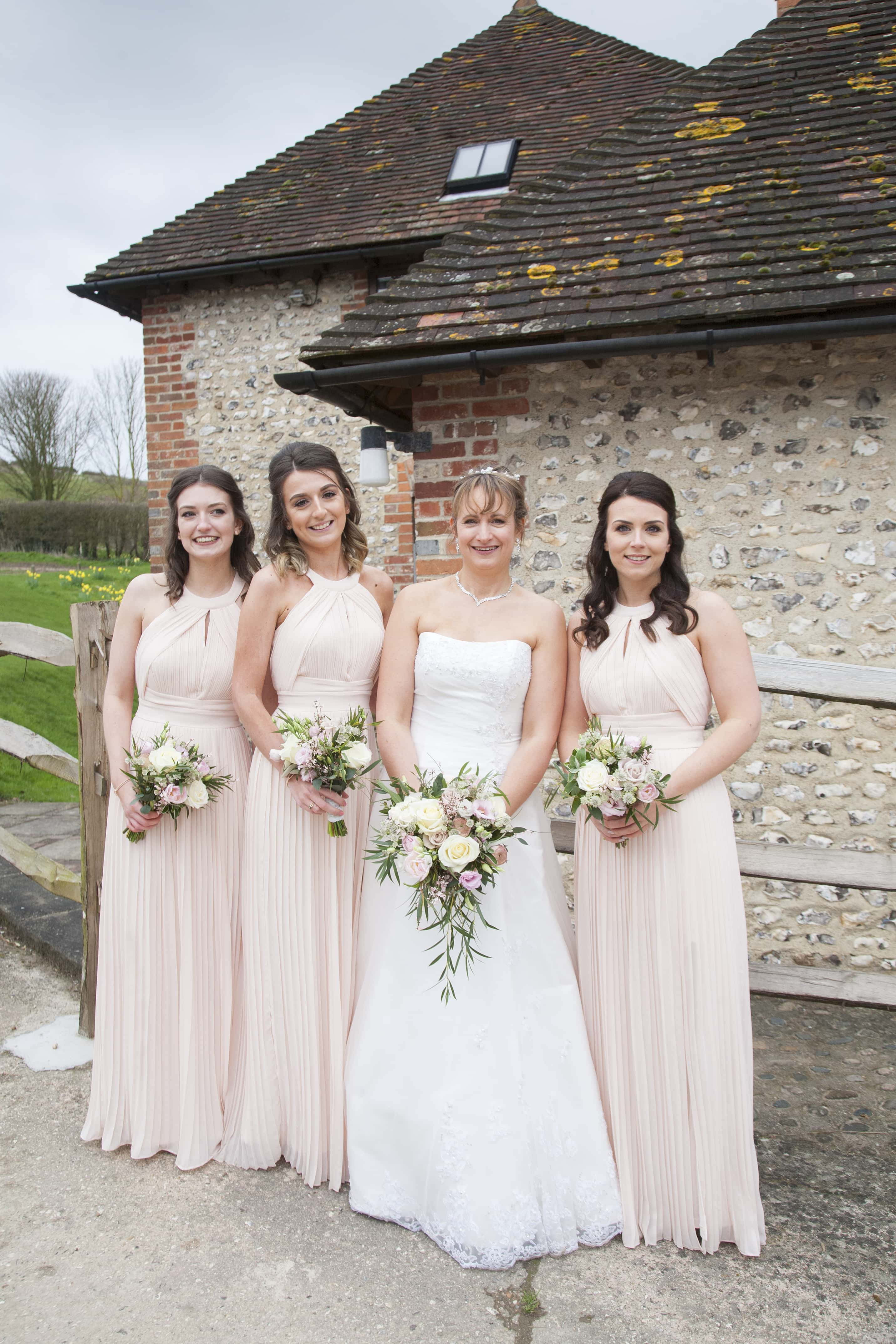 Pangdean barn April wedding. Bride and bridesmaids in nude blush pink dresses with pink and white flowers