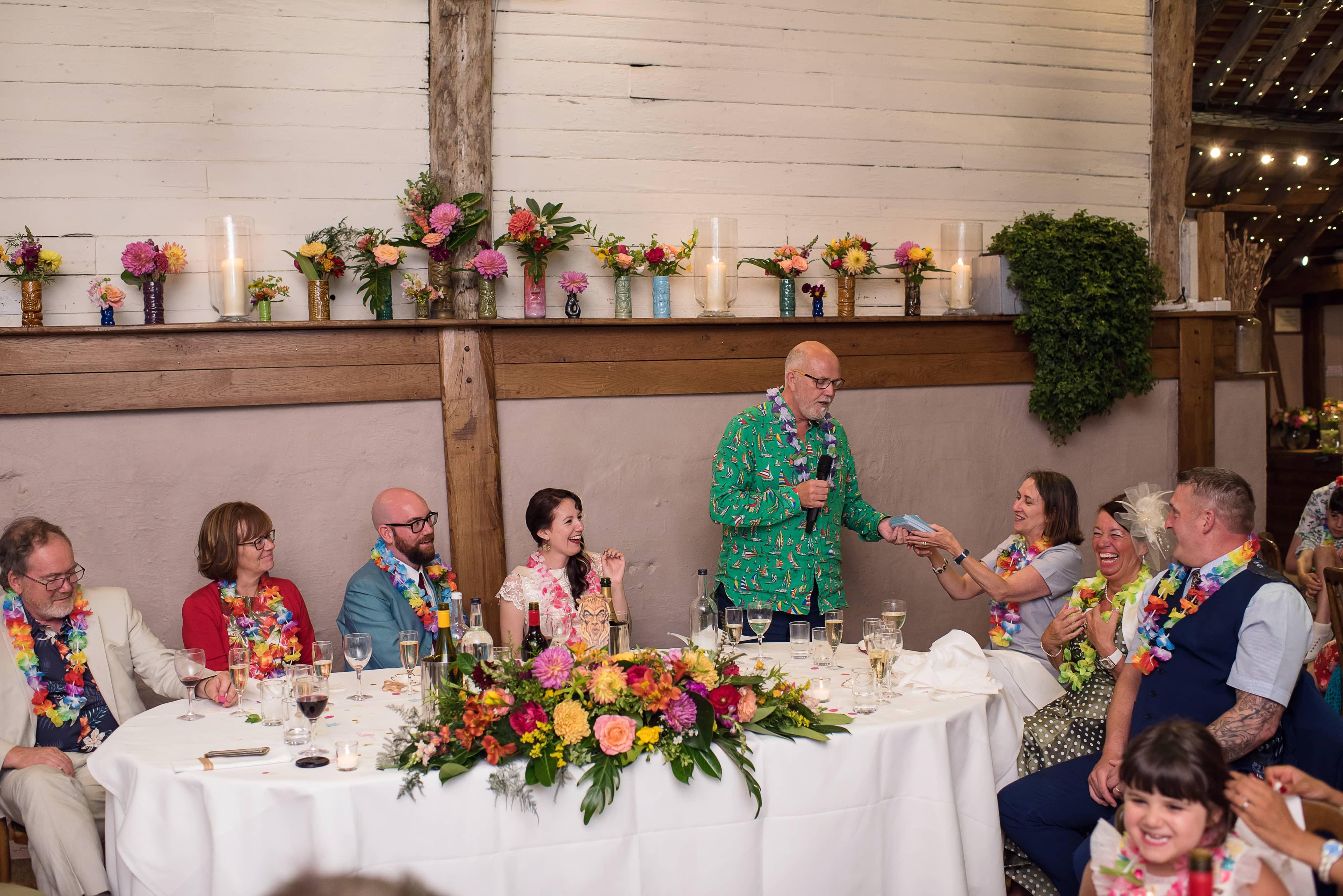 tropical Hawaiian wedding top table flowers with tiki mugs