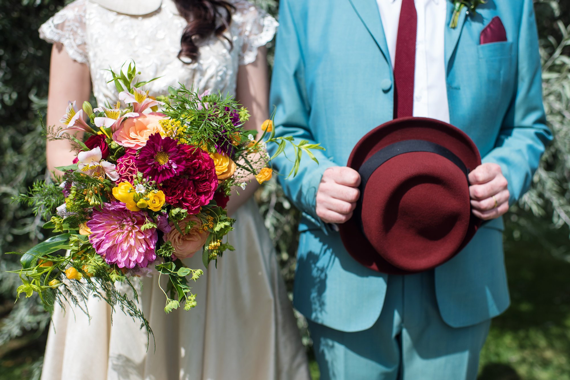 bride and groom with colourful bouquet and burgundy hat