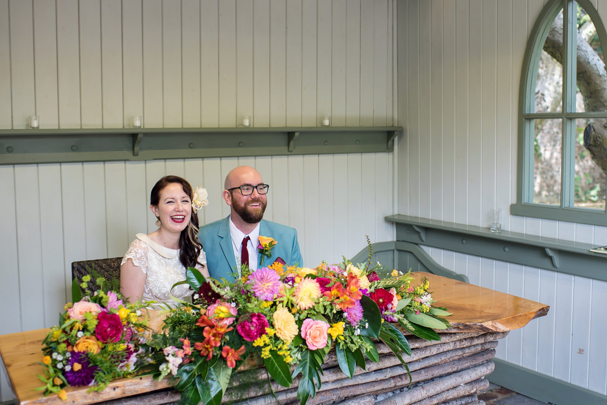 colourful outdoor wedding at Pangdean Barn. Bride and groom with bright flowers