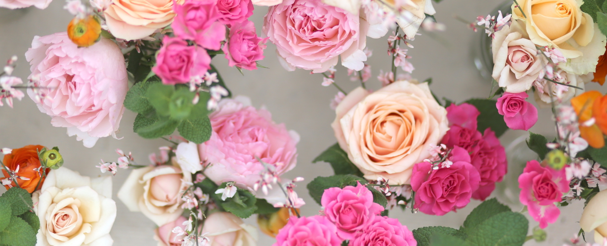 pale pink roses, hot pink spray roses with peach roses and orange ranunculus for a mothers day bouquet