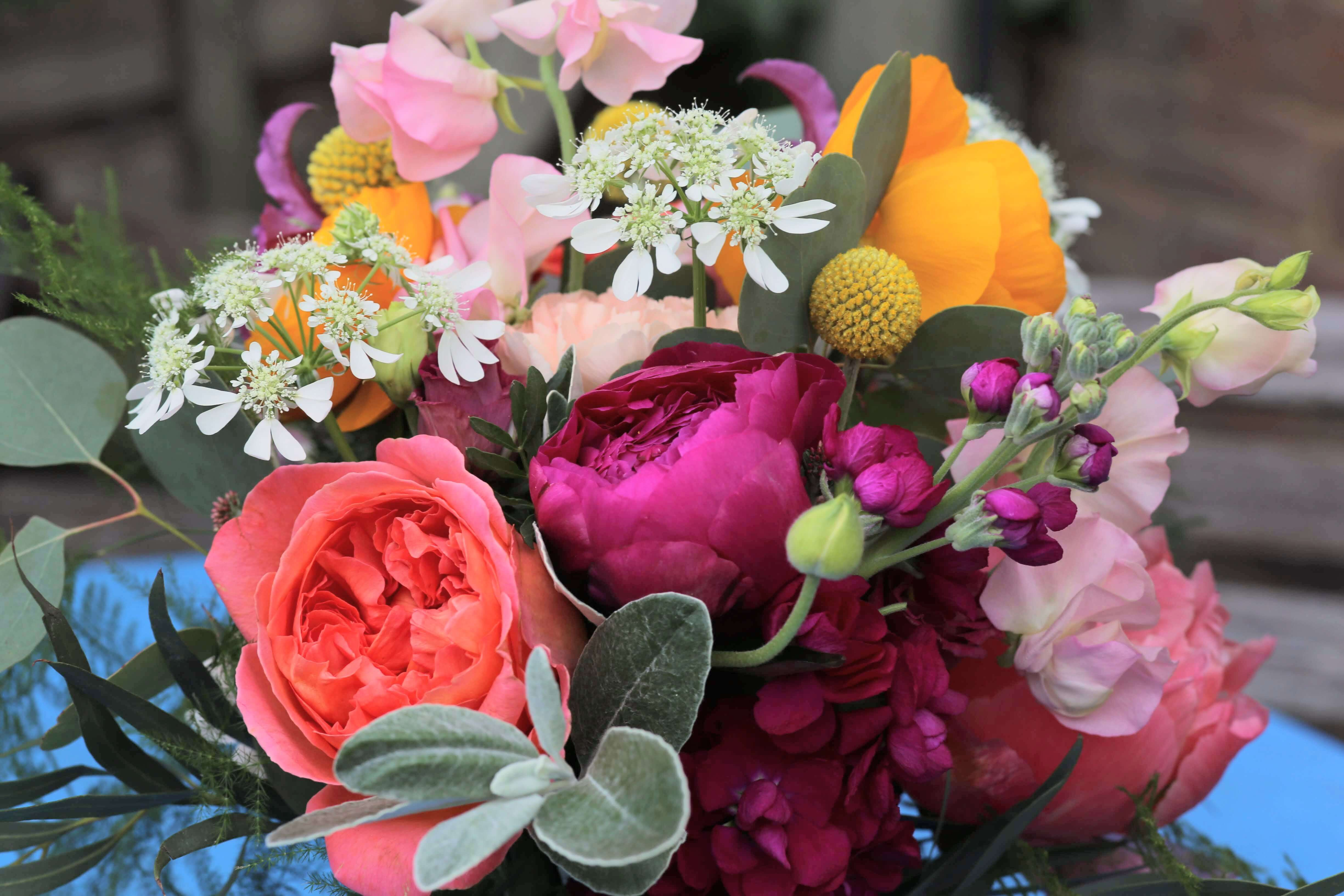 Bright and colourful bridal bouquet with peonies, ranunculus and garden roses by Bettie Rose Flowers, Sussex wedding florist