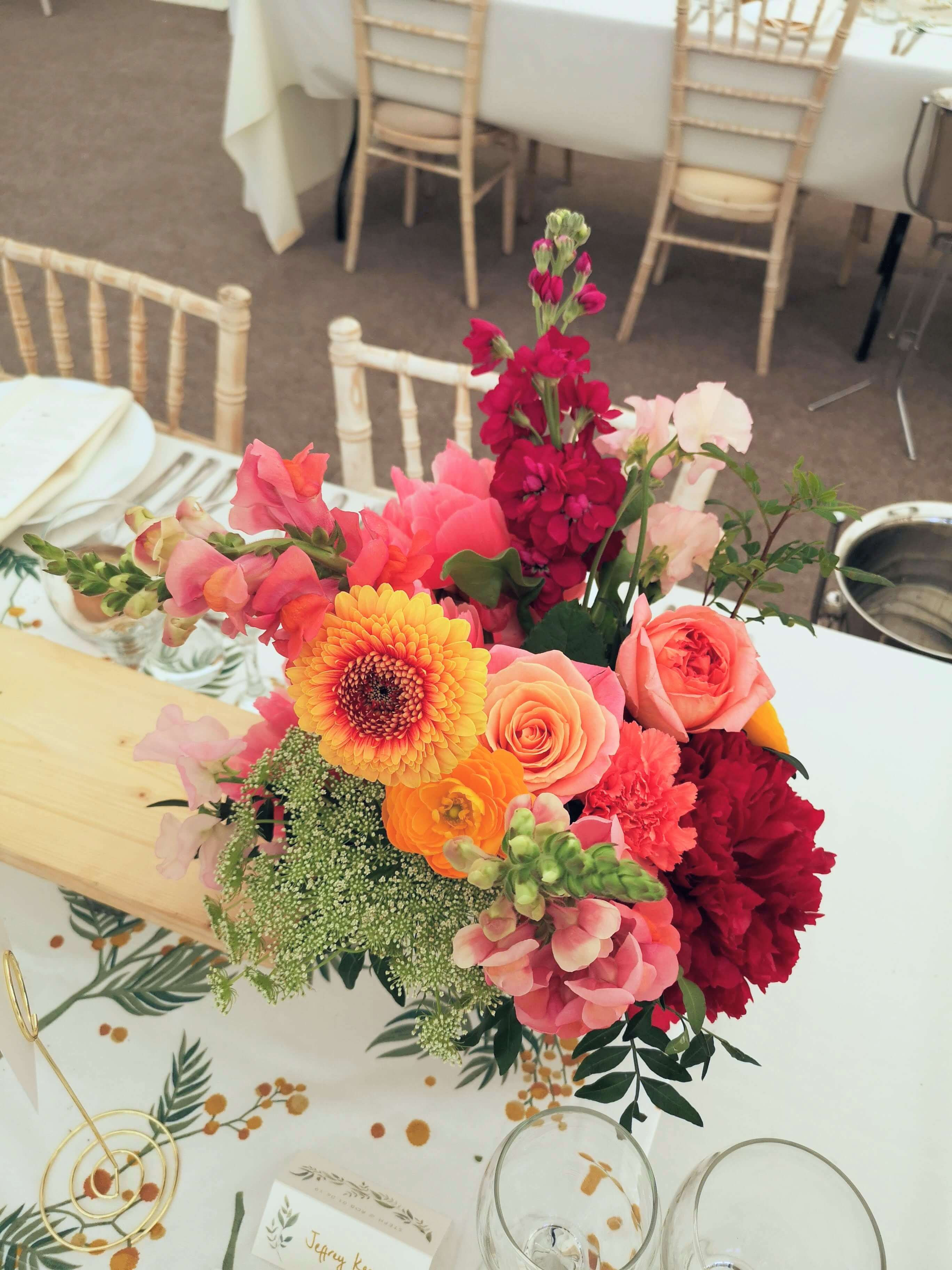 coral charm peony table centres. Sussex wedding florist.