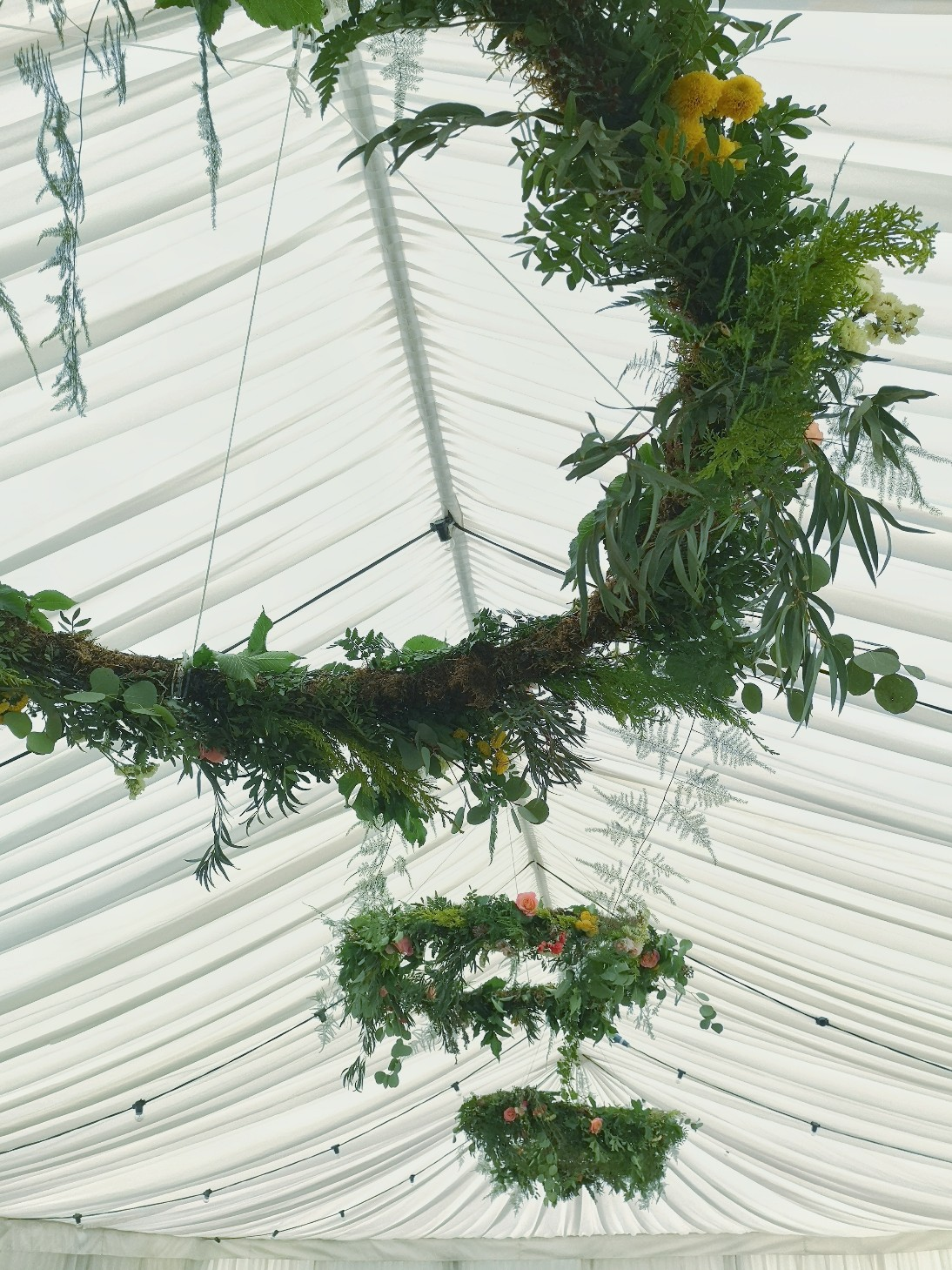 hanging foliage hoops in a wedding marquee