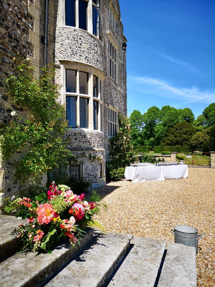 Glynde Place Wedding, outdoor drinks reception with flowers